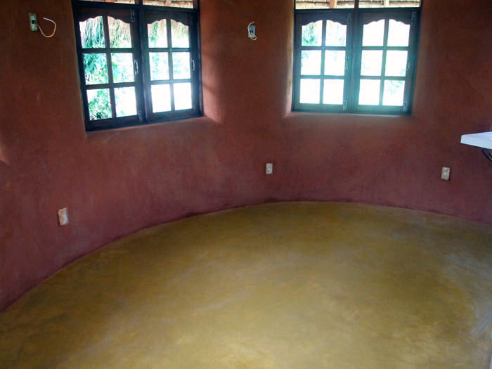 Interior view showing natural color of earthen plaster, recycled windows and yellow concrete floor.  For the floor, we troweled natural iron oxide pigment on the surface before the concrete set up.