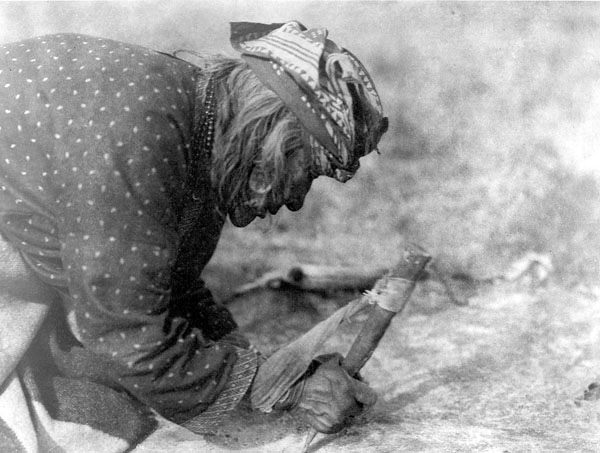 A Blackfoot women fleshing a hide with a bone in 1928